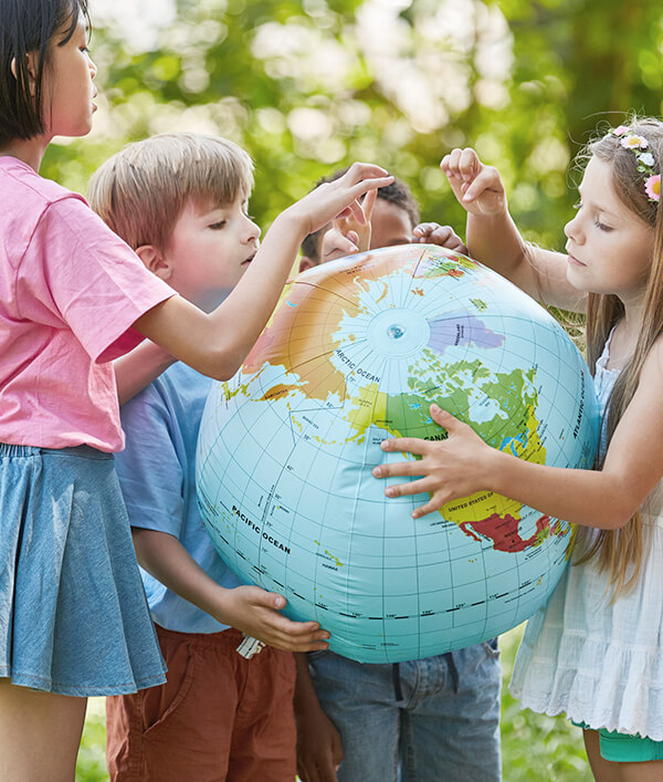 Children are learning with the help of a globe in an international kindergarten in Wroclaw